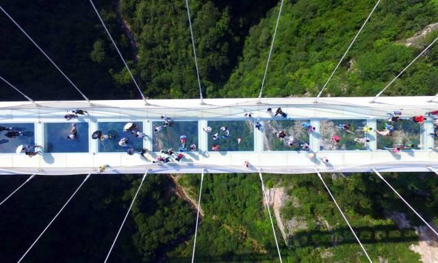 60886124_Visitors-walk-across-a-glass-floor-suspension-bridge-in-Zhangjiajie-in-southern-China27s